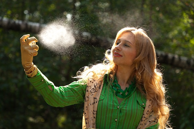 žena stříkající na sebe sprej